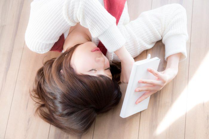 本を閉じて目を閉じる女性