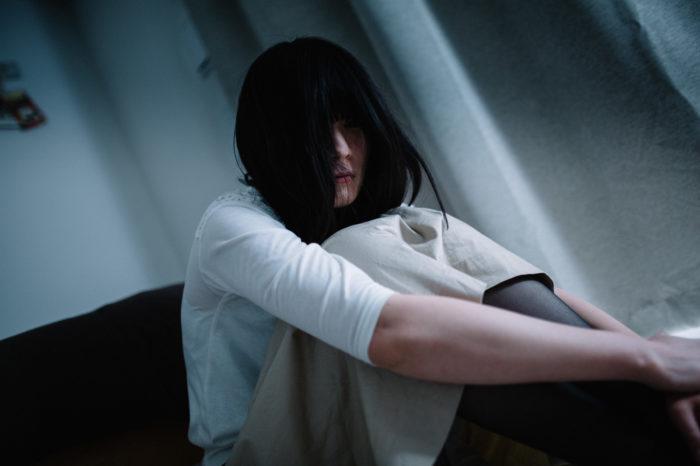 薄暗い部屋に座っている長髪の女性