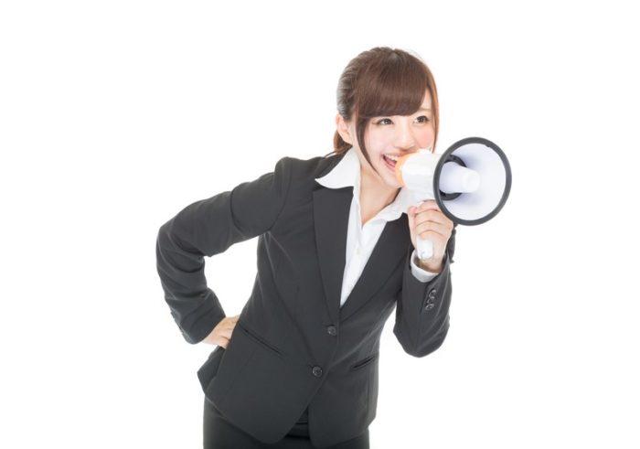 拡声器を使って大声を出す女性