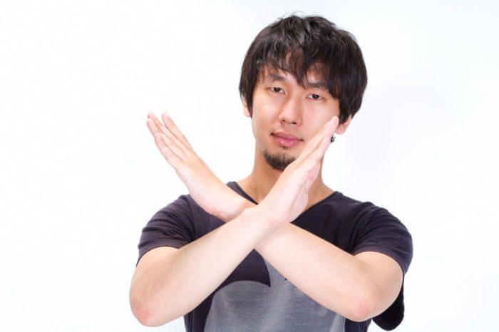 腕をバツ印に交差させる男性