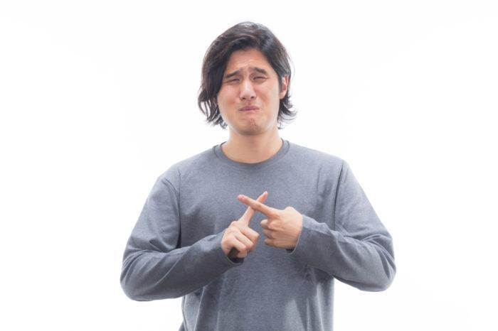 渋い表情を浮かべながら、指でバツマークを作っている男性