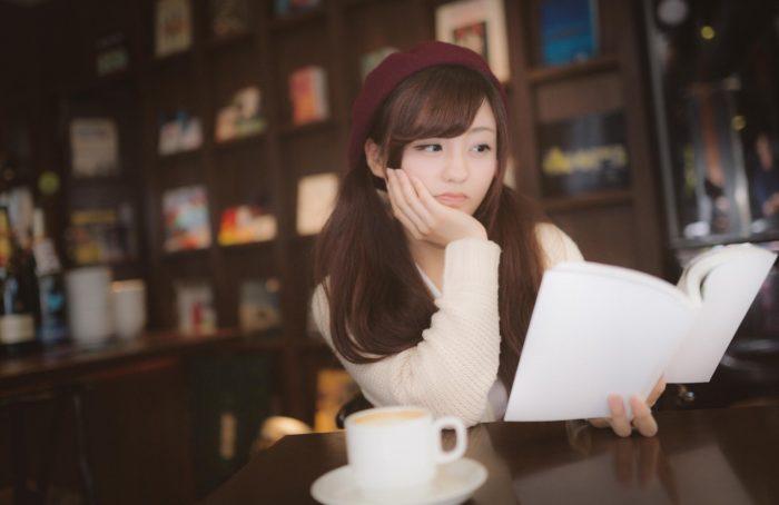 退屈そうに本を読む女性