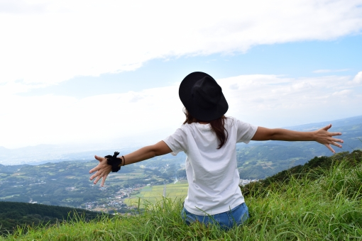 空に向かって両手を広げる女性の後ろ姿