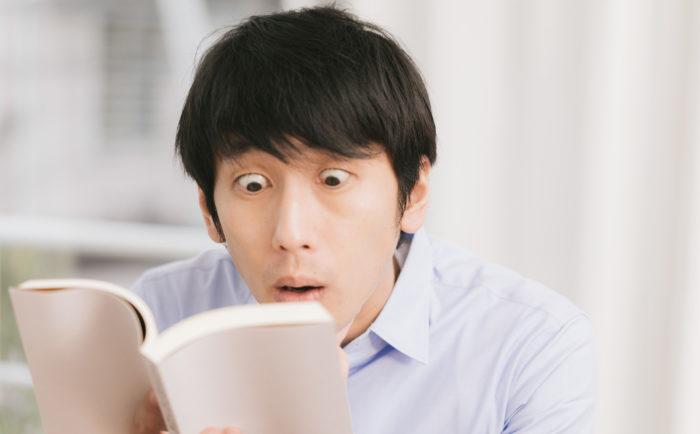 衝撃展開に驚く読書中の男性