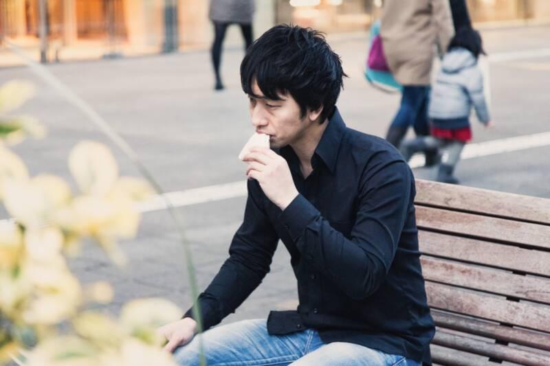 ベンチでパンを食べる男性