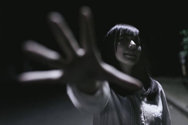 暗闇で手を伸ばす女性