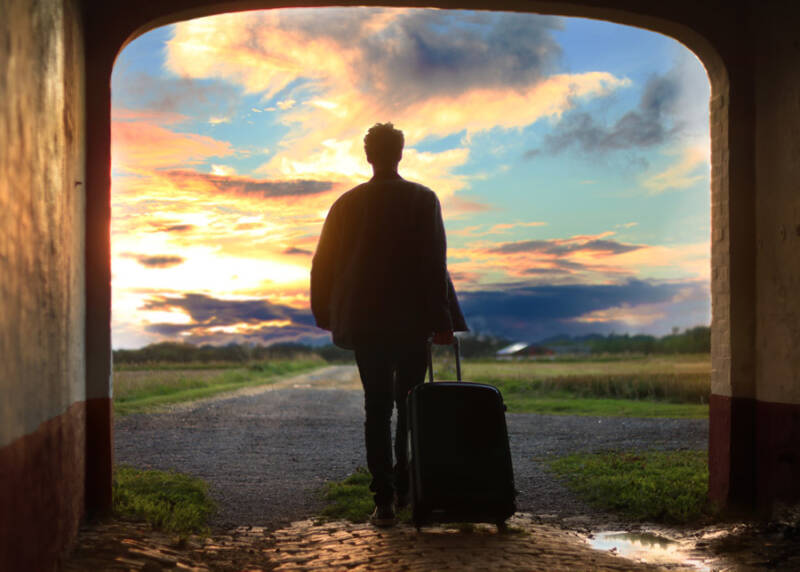 キャリーバックを引いて旅立つ男性