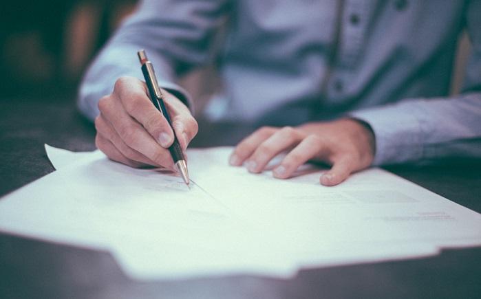 書類にペンで書きこむ男性