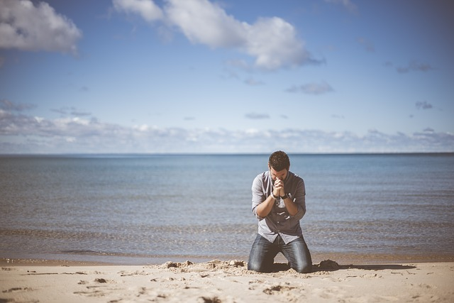 浜辺で祈る男性