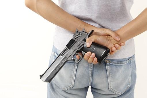 後ろに拳銃を隠し持つ男性