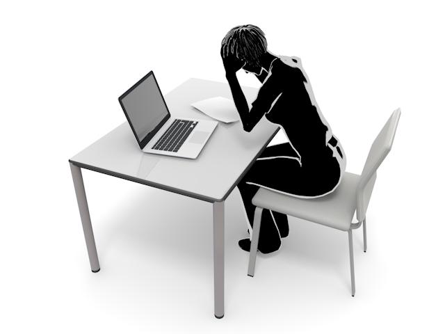 ノートパソコンの前で悩む男性