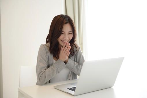 パソコンの前で嬉しそうにしている女性