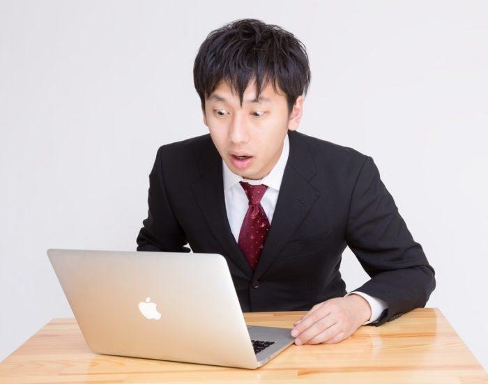 パソコン画面を見て驚く男性