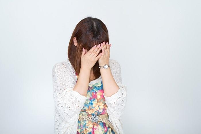 顔をおおって泣く女性