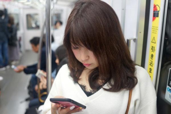 電車でスマホを操作する女性